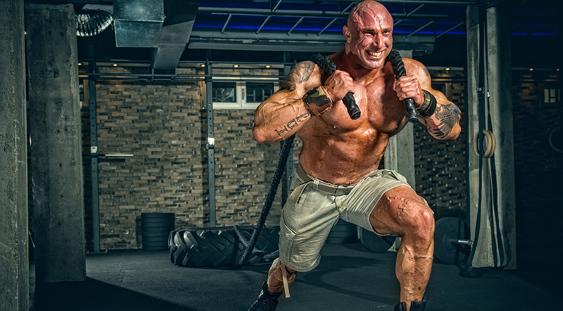 Strong Muscular Men pulling big tire with ropes
