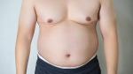 Midsection Of Shirtless Man Standing Against Wall