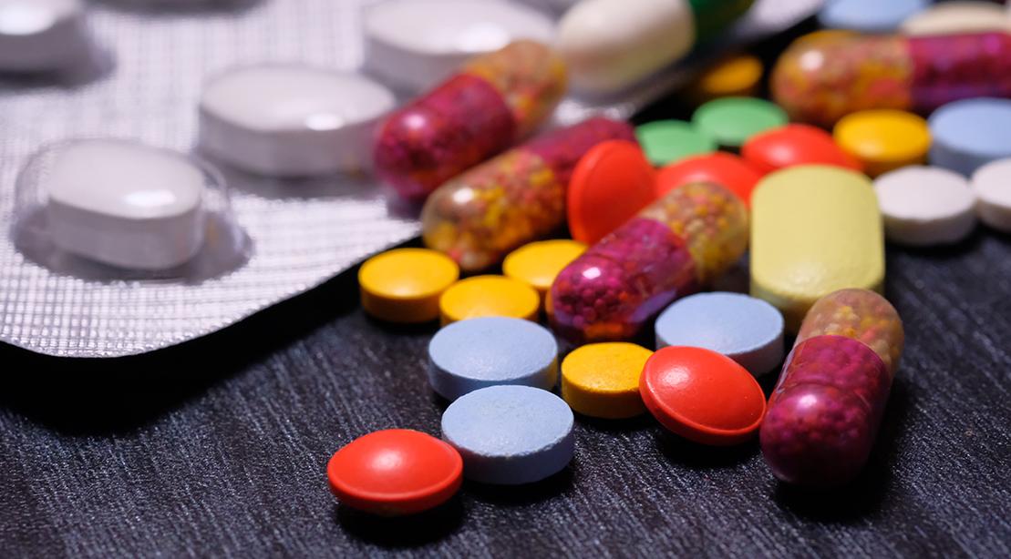 Comprimés multicolores, pilules sur la table en bois