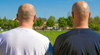 Two bald men sitting out in the sun.