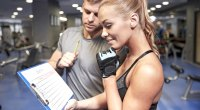 Female fitness enthusiast looking over her personal trainer training chart to build muscle