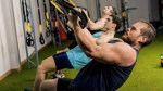 Group of fit men working out and using the important exercises TRX Inverter Row