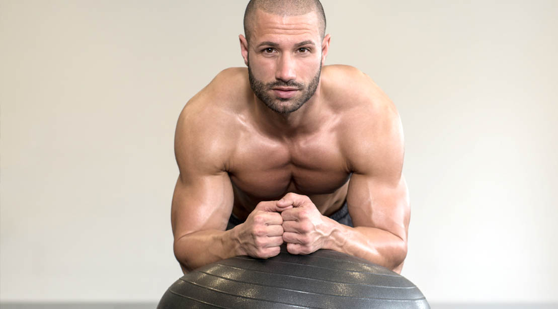 Fit man using a swiss ball to perform an important exercises for men