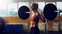 Young woman with abs performing barbell back squat