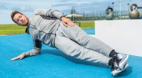 Fit man working out door doing a side plank exercise