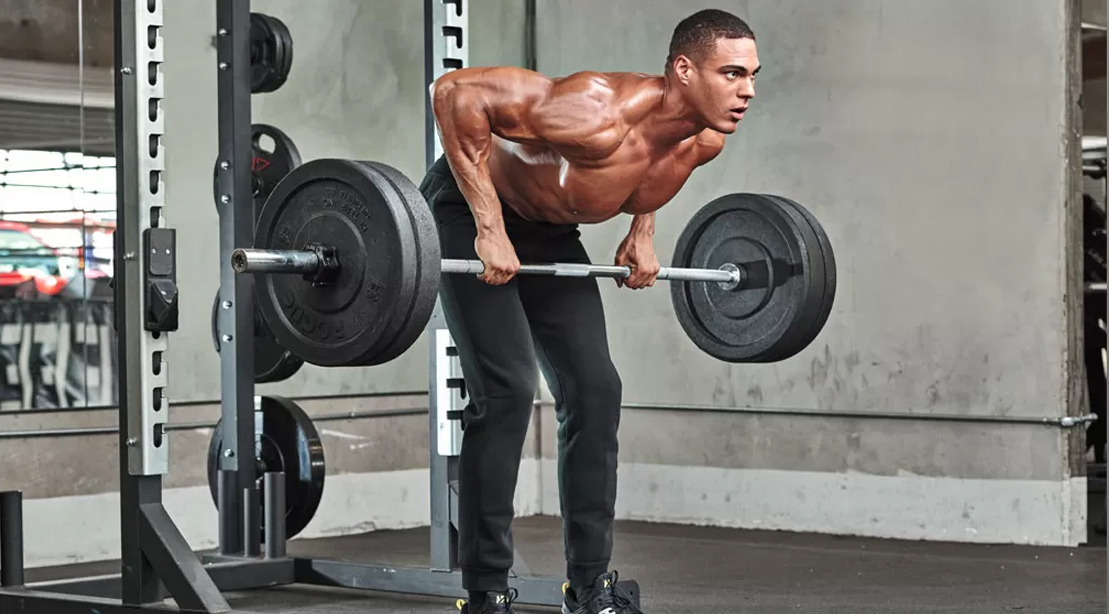 Fitness model working out his back doing a barbbell bent over row exercise