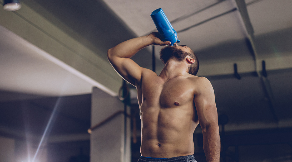 Muscular and fit man drinking a protein shake and drinking a post workout supplement