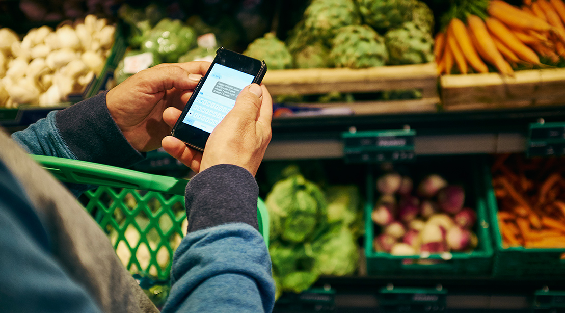 Man shopping and using smartphone in supermarket