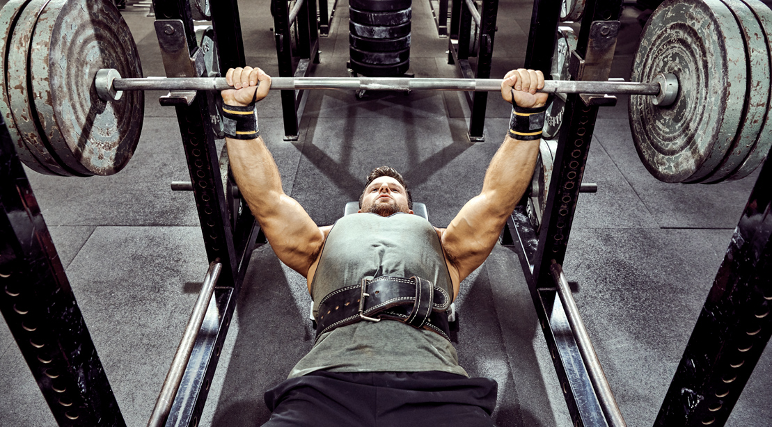 Bodybuilder and muscular man working out his upper muscles with a barbell bench press