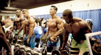 Bodybuilders in a bodybuilding competition lifting dumbbells in front of a mirro
