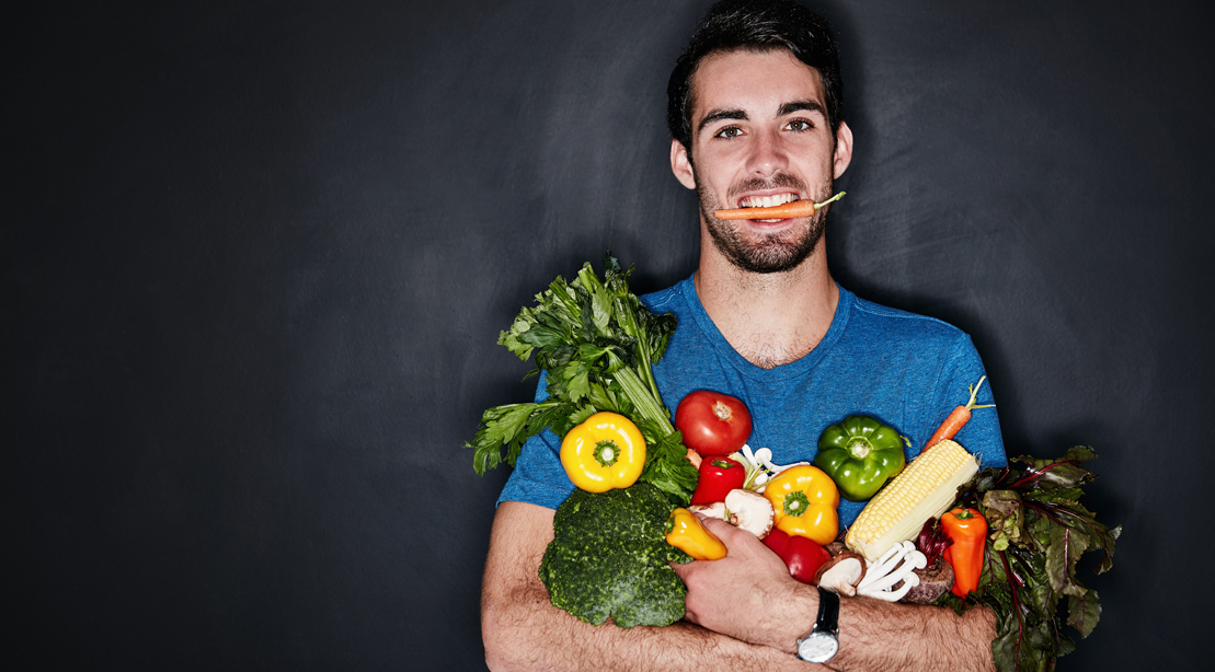 Man holding a carrot in his mouth while holding a bag of vegetable and produce for his volumetrics diet