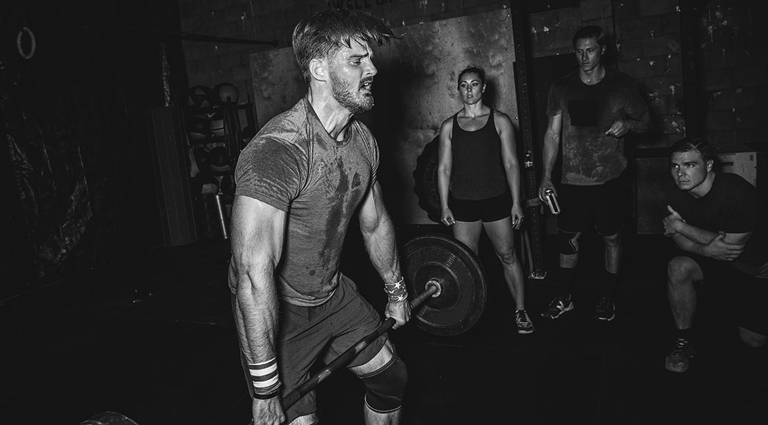 A black and white image of a Crossfitter deadlifting while sweating and exercising for power and explosiveness