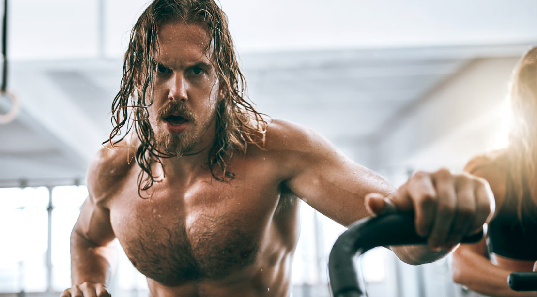 Sweaty muscular man with long hair doing cardio on an exercise bike