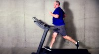 Overweight man running on a treadmill and losing fat