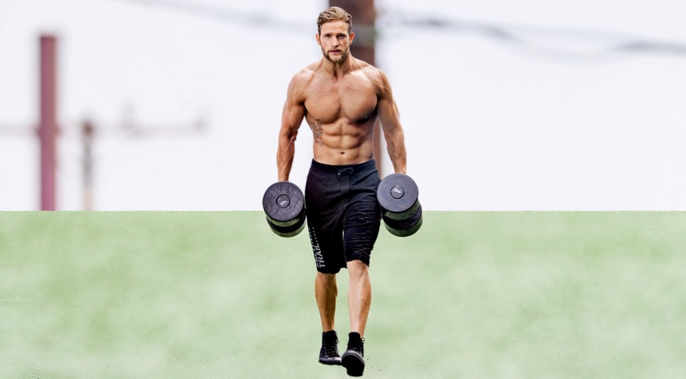 Male fitness model with a muscular core doing forearm workouts with dumbbell farmers carry exercise