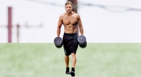 Male model with a muscular core doing forearm workouts with dumbbell farmers carry exercise