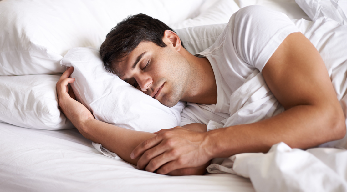 Muscular man sleeping deeply on a bed and pillow under his head