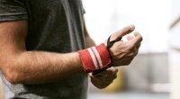 Man working out and avoiding wrist injuries using a wrist strap