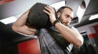 Man exercising with a sandbag on his shoulder