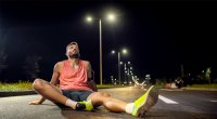 Tired male runner exhausted and resting on the road due to low energy after running due to dehydration