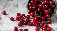 A bowl full of the superfood cherries spilling onto a table