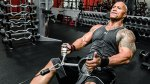 Movie star and pro wrestler The Rock working out with cable pull exercise in a gym
