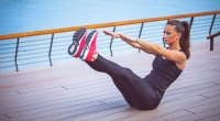 Female on a boardwalk performing v-sit exercise