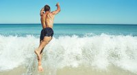 Man diving into the ocean wave on the beach as a summer activities