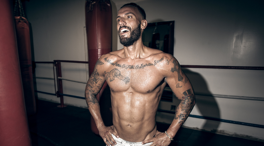 Fit man in a boxing ring feeling happy after an intense workout