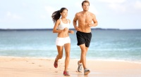 Fit couple running on the shoreline of a beach