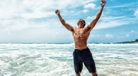 Man with abs celebrating in the ocean