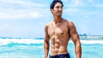 Muscular asian man with abs on the beach wading in the ocean