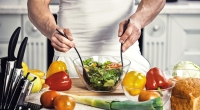 Muscular man tossing a salad in a glass bowl in his kitchen