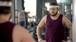 overweight man looking into the mirror in the gym