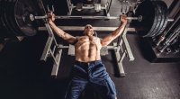 Bald man working out with a barbell bench press exercise