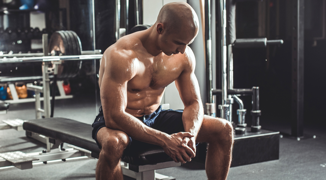 Bald-Sweaty-Man-Resting-Barbell-Bench