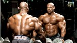 Bodybuilder Dexter Jackson looking in the mirror by the dumbbell rack