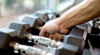 Hand grabbing dumbbell at the gym dumbbell rack