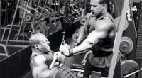 Jay Cutler spotting Phil Heath doing a cable pull down exercise