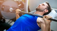 Fit muscular man working out his chest with an incline barbell bench press exercise