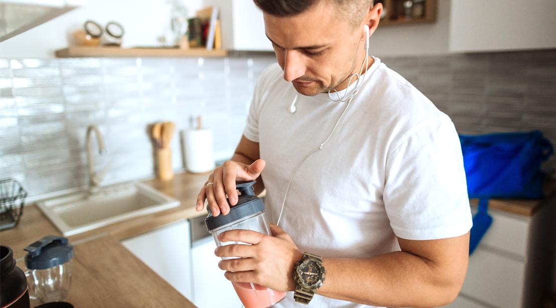 Man preparing a supplement protein shake in his kitchen