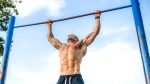 Man working out outdoors doing pull up exercise in the park on a nice blue sky day