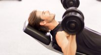 Happy and fit man smiling while doing chest exercises and workout out with the inclined dumbbell press exercise
