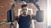 Fit male working out his chest muscles with a pec dec flye machine chest exercise