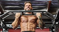 Fit muscular man working out his back and upper body doing a chin up