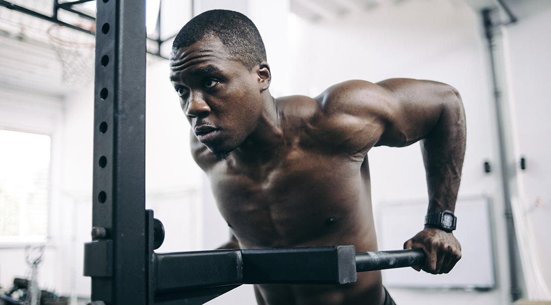 Muscular black man working out his arms and back by doing dip exercise