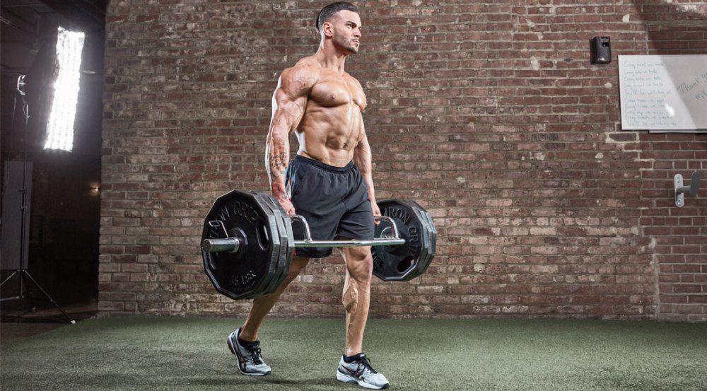 Muscular man working out his forearms and arms with a trap bar carry