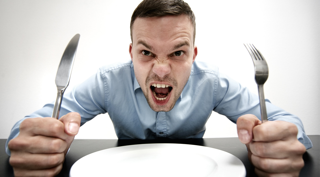 Angry man hungry and screaming while holding a fork and knife in front of an empty plate