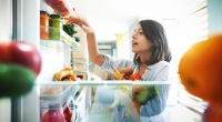Female choosing fruits and vegetables from her refrigerator