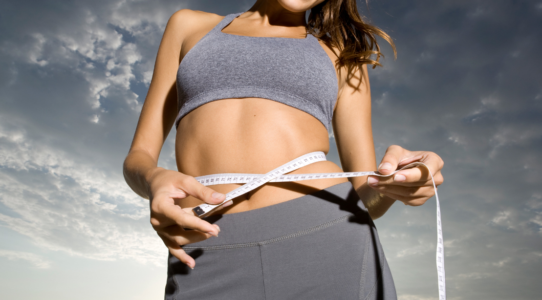 Female measuring her waistline with a measuring tape